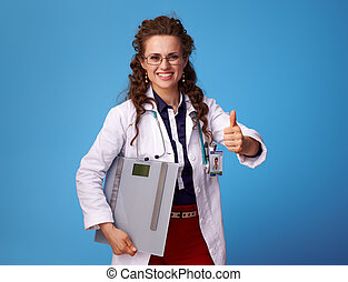 medical practitioner woman with scales showing thumbs up