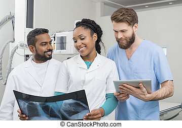 Medical Professionals With Chest X-ray And Digital Tablet In Hos