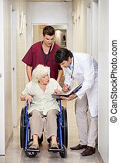 Medical Professionals With Patient In Corridor