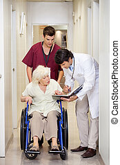 Medical Professionals With Patient In Corridor