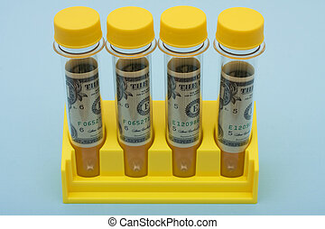 Medical Research Costs - A set of yellow test tubes on a...