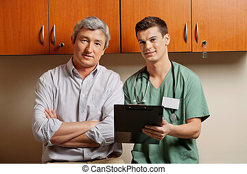 Male doctor with young resident in office