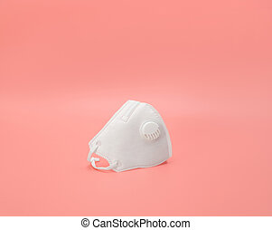 Medical respirator on a pink background. Surgical mask with filter. The prevention and protection against viruses. Coronavirus, covid-19 concept.