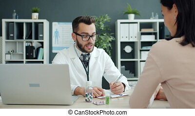 Medical specialist in glasses and uniform is talking to girl patient prescribing medication in hospital talking writing. People, clinic and healthcare concept.