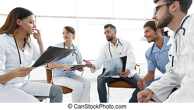 medical staff discussing x-ray of a patient sitting in the...
