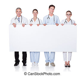Medical staff holding up a white banner - Four attractive...