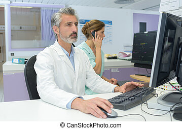 Medical staff using computer and telephone