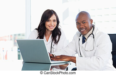 Medical staff working in front of a grey laptop while...