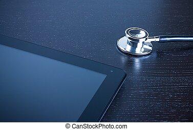 stethoscope on modern digital tablet pc on wood table