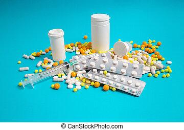 medical syringe, medicine pills, capsules, vials, on blue background. healthcare