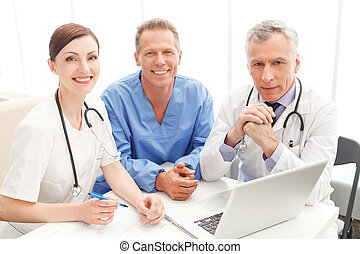Medical team at work. Cheerful medical team sitting together at the table and looking at camera