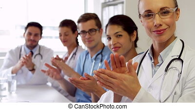 Medical team clapping at camera in the board room at the...