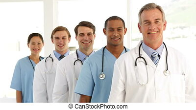 Medical team crossing arms and looking at camera at the hospital