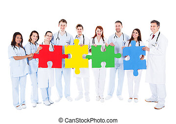 Medical team holding colorful puzzle pieces