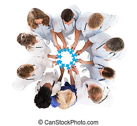Medical Team Joining Jigsaw Pieces While Standing In Huddle...