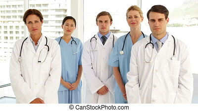 Medical team looking at camera and each other at the...