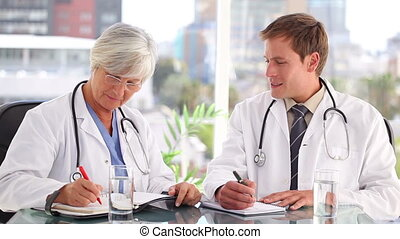 Medical team writing on their notebooks
