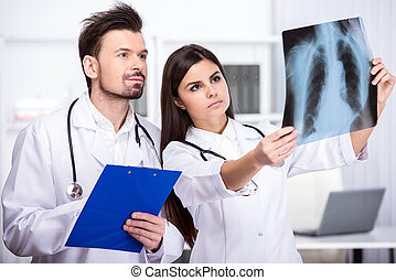 Medical - Two young doctors are looking at X-ray in medical...