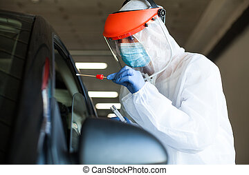 Medical worker in personal protective equipment swabbing a person in a car drive through Coronavirus COVID-19 mobile testing center,oral and nasal specimen collection procedure,health and safety