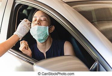 Medical worker taking nasal swab from woman in car to test for covid-19 infection.