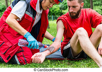 Medical worker treating burns on male's hand. First aid...