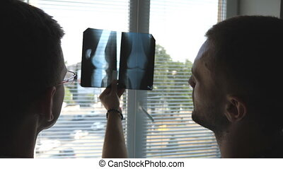 Medical workers in hospital looking and analizing x-ray prints. Medic consult with each other. Two male doctors view mri picture and discussing about it. Close up Rear back view
