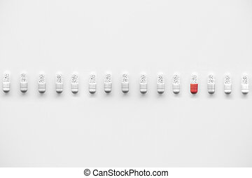 Medication capsules - Row of white medication capsules with...