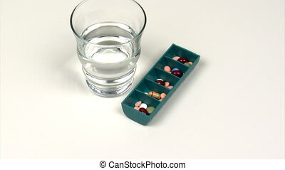 Medication - Pill box and glass of water on a rotating...