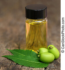 Medicinal neem leaves with essential oil in bottle on...
