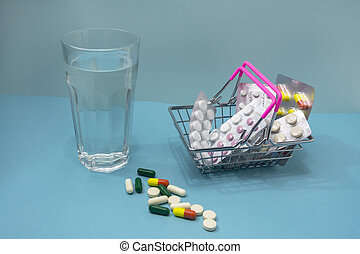 Medicinal tablets in blisters are stacked in a shopping cart. Nearby is a glass of pure water and capsules of vitamins are scattered on a blue background. Concept for pharmacy, medicine, online shopping
