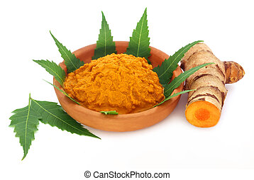 Medicinal turmeric paste with neem leaves over white...
