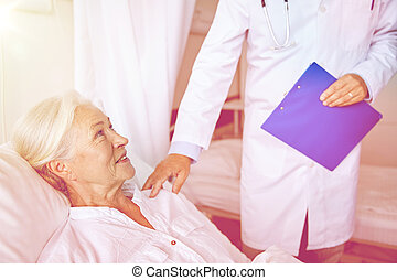 doctor visiting happy senior woman at hospital