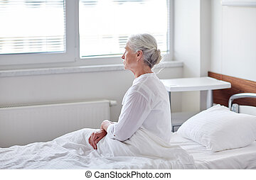 senior woman patient lying in bed at hospital ward -...