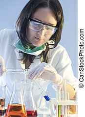 Medicine and Healthcare Concepts. Female Laboratory Staff Dealing with Flasks Filled with Chemicals Specimens During Scientific Experiment in Lab