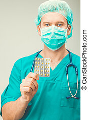 Medicine and healthcare - surgeon holding pills in one hand
