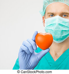 Medicine and healthcare - surgeon in green uniform holding toy heart with one hand