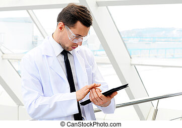 Medicine and science - A young male doctor holding a tablet...