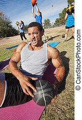 Medicine Ball Sit-Ups - Serious muscular man doing sit-ups ...