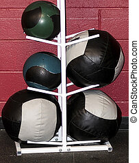 Medicine balls on a white rack in front of a red wall
