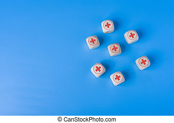 Medicine concept with icons on wooden cubes, blue background.