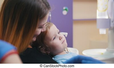 Medicine, dentistry. Female dentist examines the oral cavity of little baby
