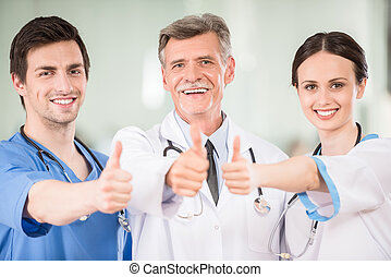Experienced male doctor with medical interns at clinic.