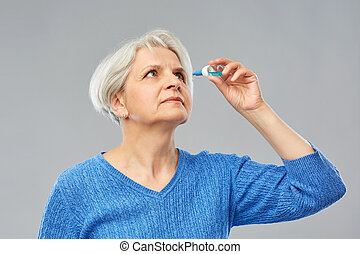 senior woman with dry eye syndrome using drops