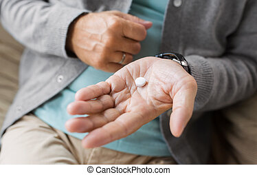 close up of senior man hand with pill