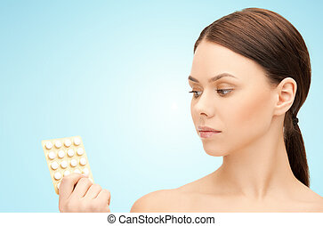 young woman with pills over blue background