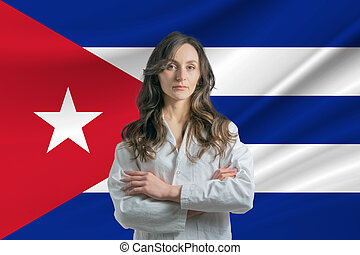 Medicine in Cuba Happy beautiful female doctor in medical coat standing with crossed arms against the background of the flag of Cuba