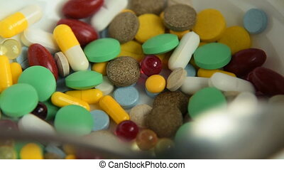 Close-up shot of taking pills with a spoon from the plate. Medicine overdose metaphor