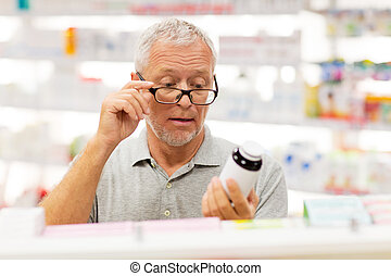 senior male customer with drug at pharmacy
