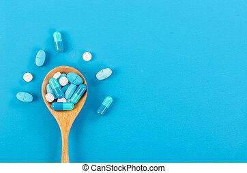 Medicine pill in wooden spoon.