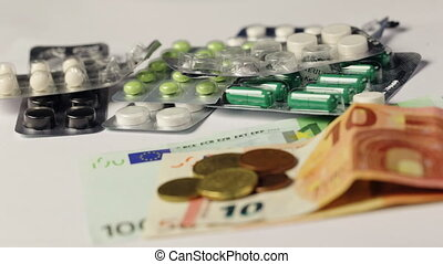 Medicine pills or capsules with money and syringe on white background. Pharmacy business, drug cost. Cash currency, expensive bill. Finance concept of pharmaceutical medication. Euro coins.